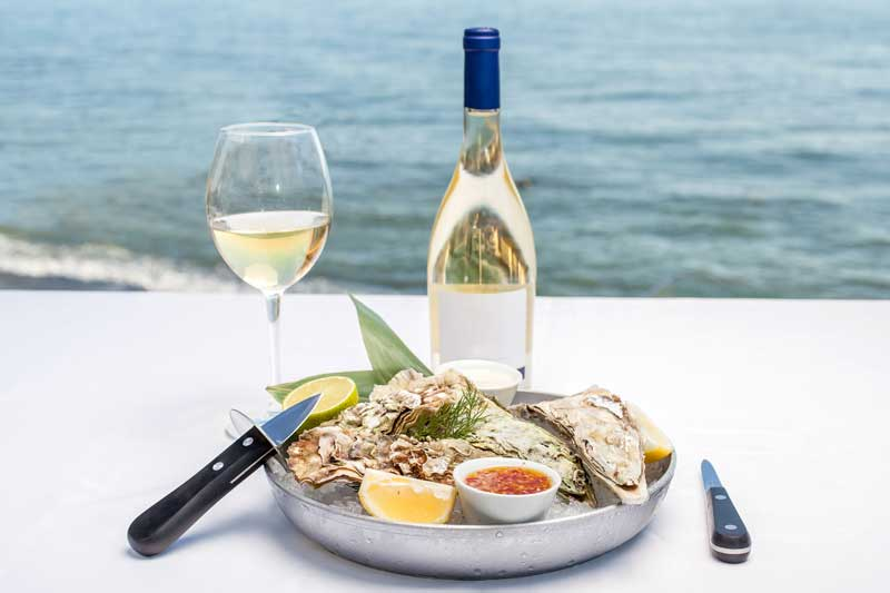 Oysters and a bottle of wine on a white table overlooking the water.